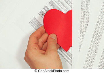 Hand pulls the heart hidden among the papers