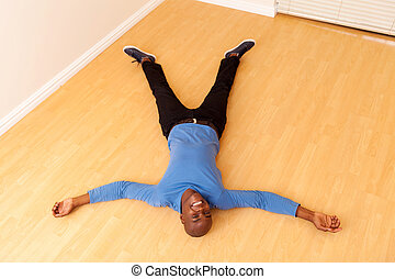 young african man lying on the floor - overhead view of...