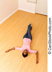 top view of african woman lying on floor in her new house