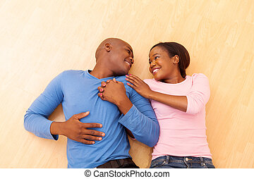 african american couple lying on the wooden floor - romantic...