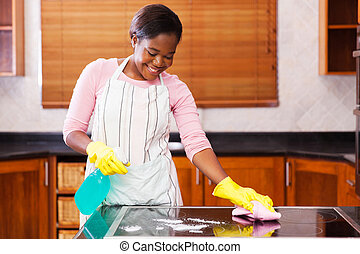 young african woman doing house chores - pretty young...
