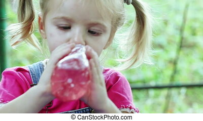 Child drinks from bottle - Girl child outdoors drinking from...