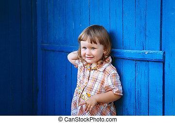 Portrait of happy smiling cute little girl against the blue wall