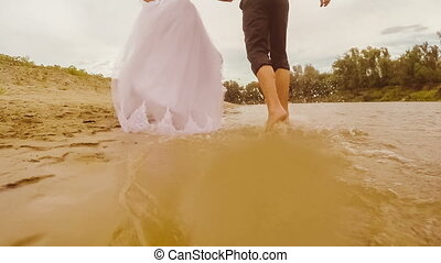 Young couple bride and groom running through the water view...