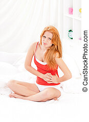 Girl on bed - Young woman sitting on the bed with pain