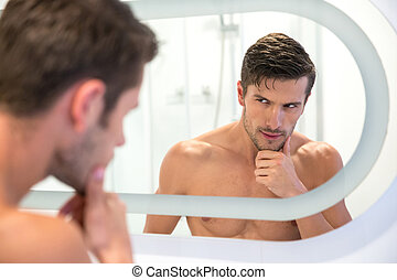 Man looking at his reflection in the mirror - Portrait of a...