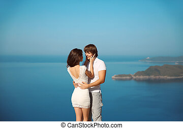 Passionate couple in love over sea and blue sky background. Enjoyment. holidays, vacation, love and happiness concept.