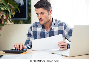 Man with calculator checking bills - Portrait of a man with...