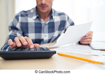Man with calculator checking bills - Closeup portrait of a...