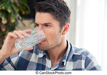 Man drinking water - Portrait of a young man drinking water...