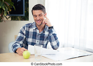 Portrait of a happy man checking bills on laptop at home