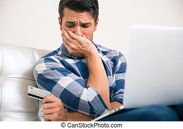 Upset man holding credit card at home
