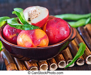 fresh nectarine in bowl and on a table
