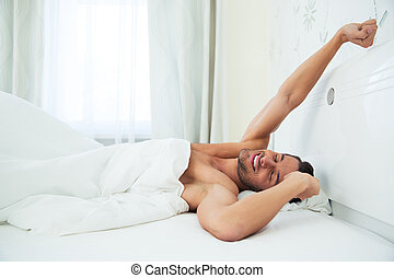 Man stretching hands in the bed - Portrait of a young man...