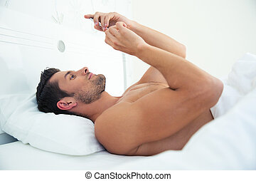 Man using smartphone in the bed - Portrait of a young man...