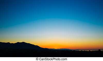 Dark Silhouette of Mountains on colorful sunrise sky background.