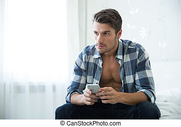 Man sitting on the bed with smartphone - Portrait of a...