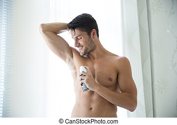 Man with deodorant at home - Portrait of a handsome man with...