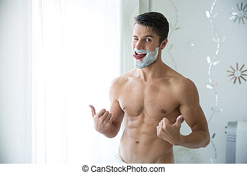 Man with foam on face showing thumbs up