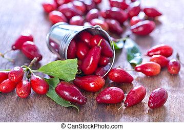 cornus - fresh cornus on the wooden table, red cornus