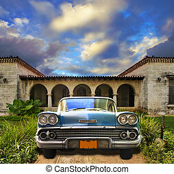 Old car parked in tropical house, cuba - Front view in...