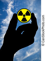 Hand with radiation sign and sky - The silhouette of a mans...