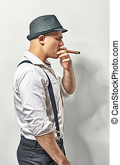 Stylish man smoking cigar - Side view of a stylish young man...