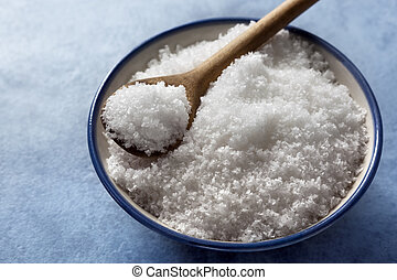 Sea Salt Flakes - Bowl of sea salt flakes with a wooden...