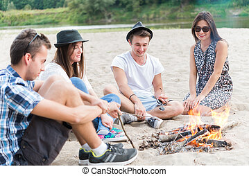 Young Adult Friends Hanging Around At Bonfire On Sandy Beach...