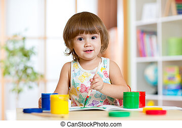 kid painting at home - pretty kid girl painting with...
