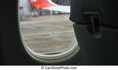 Raindrops on the air plane window with blur airport outside...