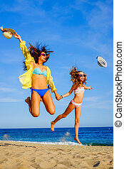 Young girls in swimwear jumping on beach. - Close up action...