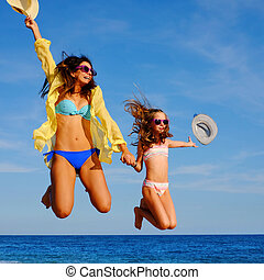 Young girls on holiday jumping with hats. - Close up action...
