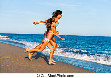 Young girls running towards waves. - Action portrait of...