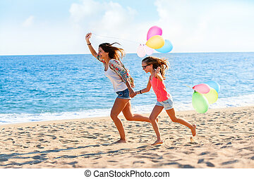 Young girls running with balloons on beach. - Action...