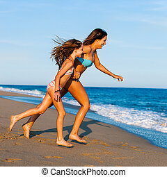 Young Mother running with daughter on beach. - Action...