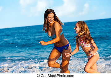Young women having great time on beach. - Action portrait of...