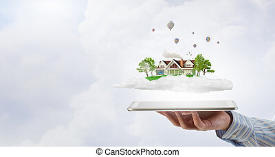House model - Male hands holding tablet pc with house model...