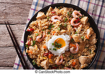 nasi goreng with chicken, prawns and vegetables closeup...
