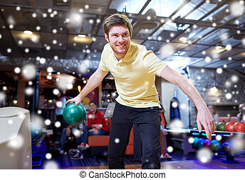 happy young man throwing ball in bowling club - people,...