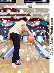young man throwing ball in bowling club - people, leisure,...