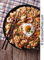 nasi goreng with chicken, prawns, egg and vegetables closeup...