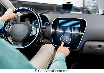 close up of man driving car with audio system - transport,...
