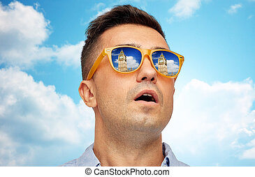 face of man in sunglasses looking at big ben tower - travel,...