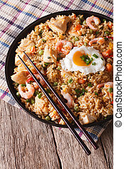 fried rice with chicken, prawns, egg and vegetables closeup...
