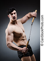 Muscular strong man with nunchucks