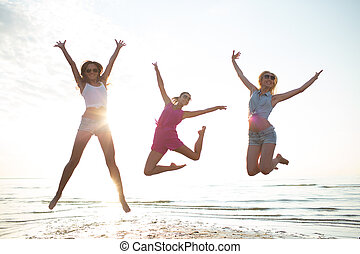 happy female friends dancing and jumping on beach -...