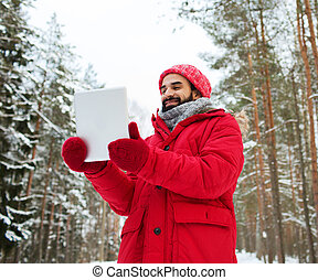 happy man with tablet pc in winter forest