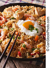 nasi goreng with chicken, shrimp and vegetables close-up...