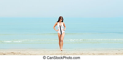 young woman in swimsuit posing on beach